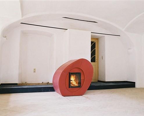 Kachelofen Niederösterreich 2: Roter Ofenkörper, dessen Linien vom historischen Raum beeinflusst wurden, Kacheln mittels eigens angefertigter Holzform gebaut, großes Sichtfenster rückwertig stehend gemauerter Speicher.