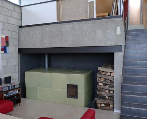 Kachelofen Niederösterreich 7: Grüner Ofenkubus, leicht aus dem Winkel, Kacheln mittels eigens angefertigter Holzform gebaut, großes Sichtfenster.