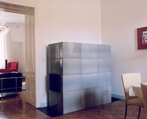 Kachelofen Wien 1: Blau glänzender Ofenkubus mit schwarzer Metallofentür, auf schwarzer Metallplatte stehend.