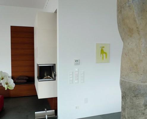 Heizkamin Niederösterreich 1: Heizeinsatz mit Ecksichtfenster, Ofenoberfläche mit Limestone-Grossformatplatten, schwebend an der Wand aufgehängt.