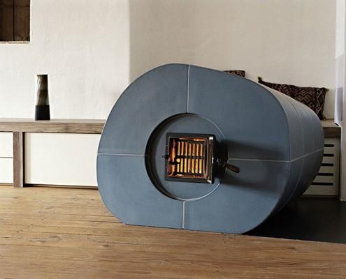 Kachelofen Niederösterreich 1: Blaue Ofenwalze freistehend im Raum, Kacheln mittels eigens angefertigter Holzform gebaut, Zugsystem befindet sich hinten rechts an der Wand stehend.