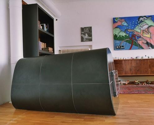 Kachelofen Niederösterreich 4: Schwarze Ofenwalze lang gestreckt, Kacheln mittels eigens angefertigter Holzform gebaut, Schwarz matt bzw. schwarz glänzend (Front) glasiert.
