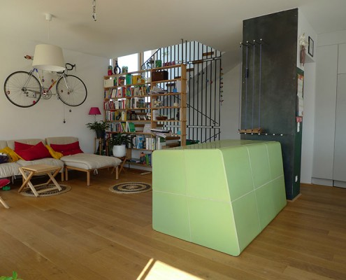 Kachelofen Niederösterreich 9: Asymmetrisch abgerundeter Ofenkubus, Kacheln mittels eigens angefertigter Holzform gebaut, mit Sichtfenster, Holzlager in Metall raumhoch an der Kaminwand.
