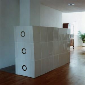 Kachelofen Oberösterreich 2: Weiss glänzender Ofenkubus, langgezogen und nach hinten hin leicht aus dem Winkel, mit großem Sichtfenster und elektronischer Abbrandsteuerung, Kacheln mittels eigens angefertigter Holzform gebaut.