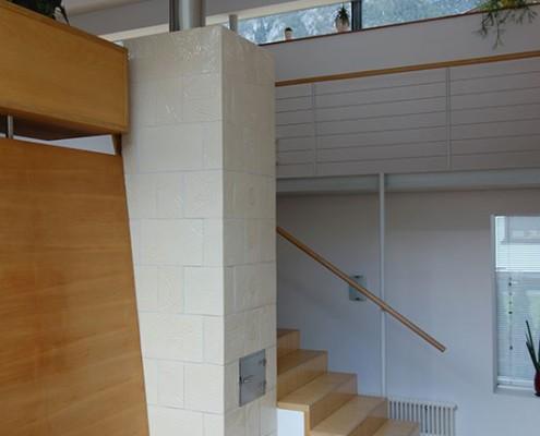 Kachelofen Tirol 1: Stehender Turmofen über 2 Stockwerke, Kacheln transparent glasiert mit Struktur, Nirosta Ofentüren, zwischen Stiege und Bank eingebettet.