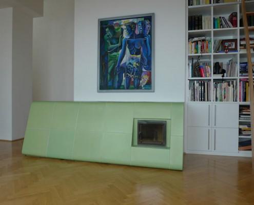 Kachelofen Wien 2: Liegender grüner Ofenkörper mit integriertem Holzlager und Sichtfenster, Kacheln mittels eigens angefertigter Holzform gebaut, abgerundete und etwas auskragende Form.